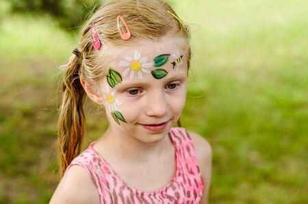 Photo pour Little girl with floral face painting to be done - image libre de droit