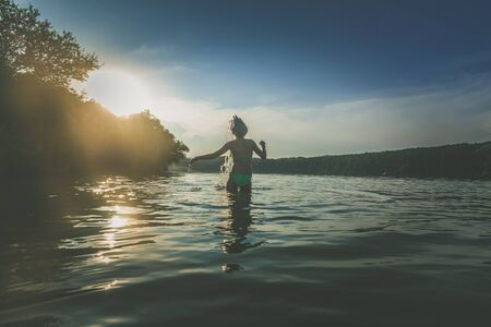 Photo for cute girl with long blond hair having fun in pond in magic golden hour time - Royalty Free Image