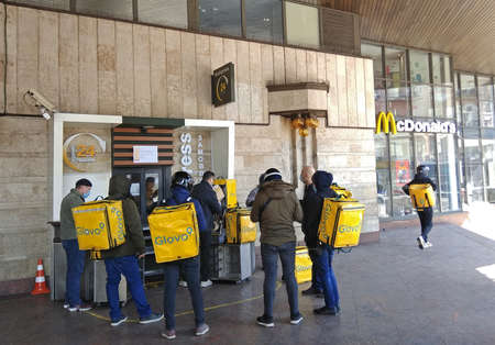 Kyiv, Ukraine - April 3, 2020: Couriers of Glovo Delivery Service waiting in a line at McDonalds Express during COVID-19 quarantine in Kyiv, when all restaurants work only in delivery mode