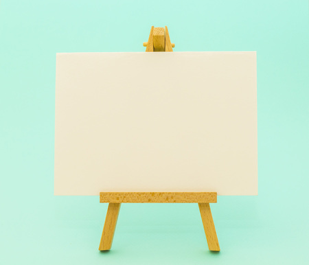 White paper on little easel on colorful aquamarine background