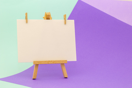 White paper on little easel on colorful violet and aquamarine background