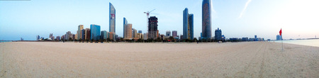 Abu Dhabi, United Arab Emirates - March 14, 2015: Skyline with Skyscrapers in Abu Dhabi, United Arab Emirates from the public beach at the Corniche. White beach and blue clear water in the front.
