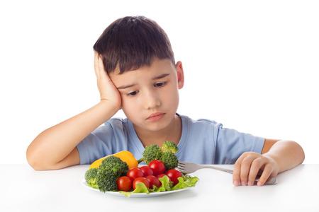 Sad boy doesn't want eat healthy vegetables