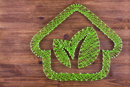 Concept of green eco-friendly house on wooden background. Handmade string art.