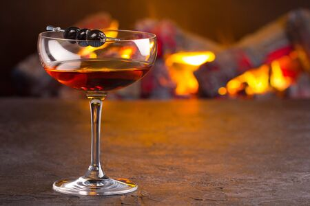 Photo for A glass of classic Manhattan cocktail on fireplace background - Royalty Free Image