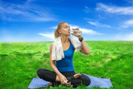 Portrait of a young woman refreshing during yoga workout at the carpet  Outdoor