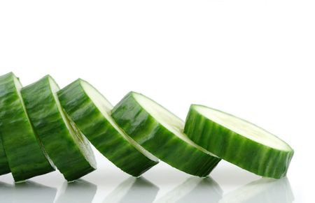 Cucumber slices reflecting in a white background.