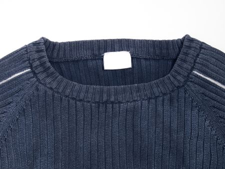 Blue sweater with empty label isolated on white
