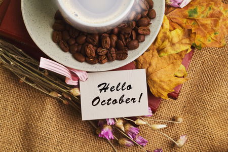 Tag with the words hello october and the cup of coffee lying on the books with dry yellow maple leaves and everlasting flowers on sackcloth background