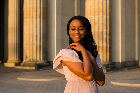 The young black beautiful woman with afro curly dark hair smiling positively with closed eyes. Woman wearing gentle beige dress and standing near big colums in the sunrise.