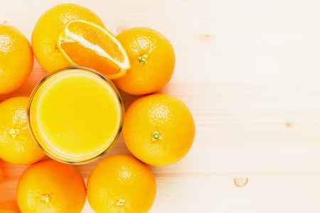 Glass of freshly pressed orange juice with oranges and sliced orange part on wooden background. Healthy lifestyle concept. View from above. Copy space fot text.