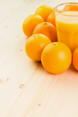 Glass of freshly pressed orange juice with oranges on wooden background. Healthy lifestyle concept. Copy space for text.