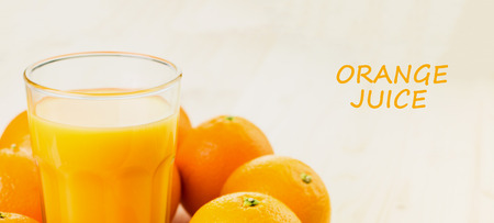 Glass of freshly pressed orange juice with oranges on wooden background. Healthy lifestyle concept with text orange juice.