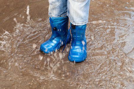 child with rain boots jumps into a puddleの写真素材