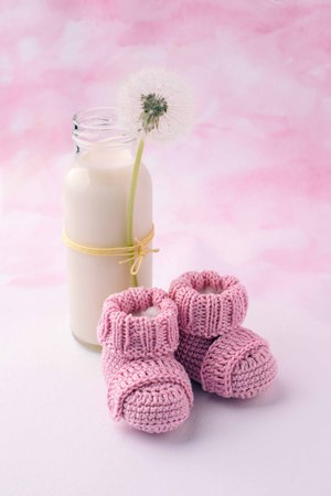 Photo pour Its a girl pink theme baby shower or sip and see party background with decorative elements - booties and milk bottle. Minimal, copy space. - image libre de droit