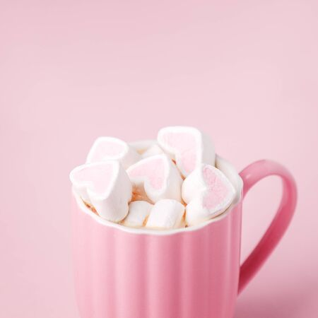 Photo pour Pink light pastel background. Cup of dark coffee, hearts shaped marshmallow. Valentine's wedding day concept. Romantic girly femininy background - image libre de droit