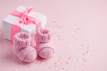 Photo for Pair of small baby socks and gift box on pink background with copy space for your warm message, baby shower, first newborn party background, copy space - Royalty Free Image
