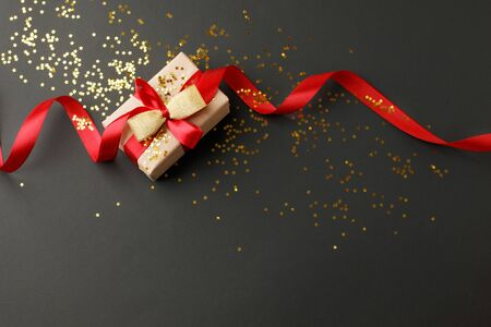 Photo pour Gift or present box and gold stars confetti on black table top view. Flat lay composition for birthday, mother day, black friday sale, xmas, christmas, new year or wedding. - image libre de droit