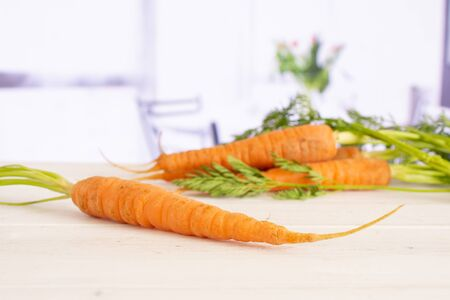 One whole fresh orange carrot in focus with greens with red flowers on white in background