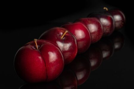 Group of six whole ripe red round plum placed diagonally in line isolated on black glass