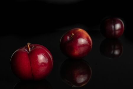 Group of three whole ripe red round plum placed diagonally in line isolated on black glass
