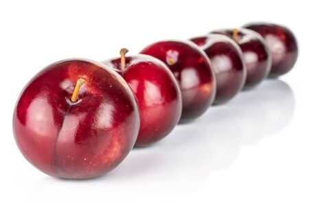 Group of six whole ripe red round plum placed diagonally in line isolated on white
