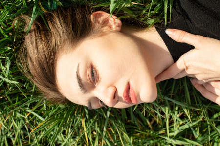 Photo pour Serious lying portrait of white girl with dark eyes on green grass - image libre de droit