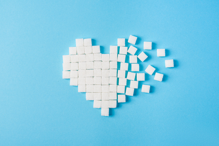 Heart made of sugar cubes on a blue background