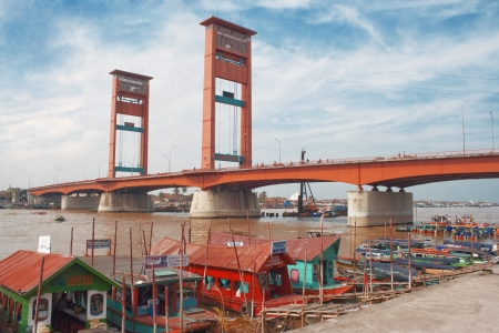 view of the Ampera bridge in Palembang, the river and the boat at the pier