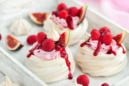 Photo pour Delicious mini Pavlova meringue cake decorated with fresh raspberry, figs  and berry sauce on white background - image libre de droit