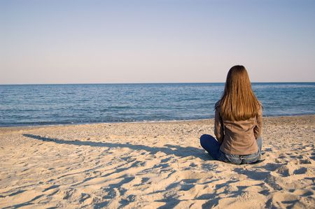 A young woman sitting alone at the seaside