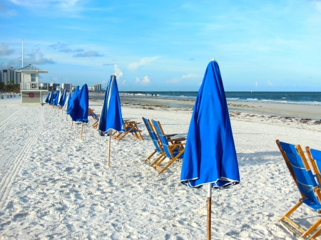 Blue beach umbrellas on Clearwater Beach Fl in morning