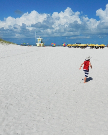 Little boy with red shirt running on white sandy Clearwater Beach FL