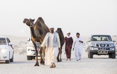 Photo pour Madinat Zayed, United Arab Emirates, December 15th, 2017: arab man with his camel at The Million Street where camels get bought and sold - image libre de droit