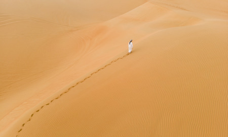 Photo pour man in traditional emirati outfit walking in massive sand dunes of Liwa desert - image libre de droit