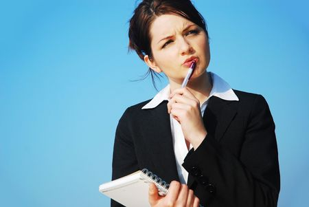 A beautiful young business woman doing with a notepad in front of a blue sky, thinking/contemplating