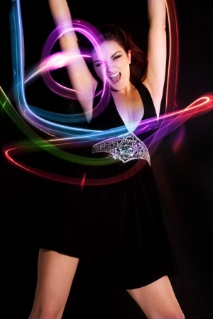 A young woman dancing with vibrant lights around her. Light painting.