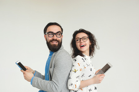 Foto de Young hipster man and woman in glasses with smartphone and tablet isolated on the blank white background - Imagen libre de derechos