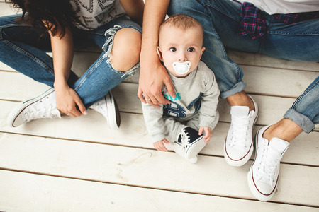 Foto de Young hipster father mother and cute baby boy sitting on rustic wooden floor over white background - Imagen libre de derechos