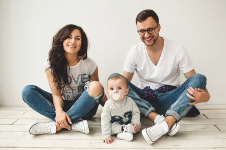 Young hipster father mother and cute baby boy sitting on rustic wooden floor over white