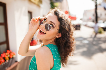 Photo pour Young woman in round sunglasses and dress with curly hair smiling over the shoulder in the city street - image libre de droit