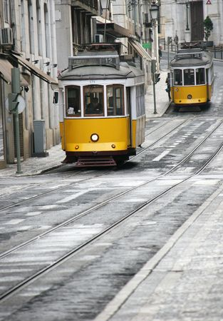 Two old yellow trams in street of Lisbon