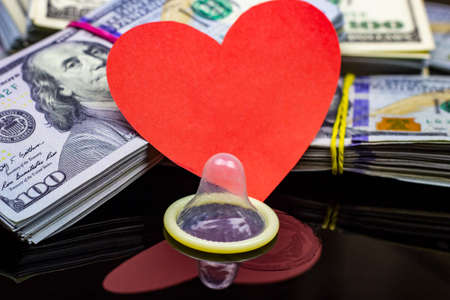 Photo pour Latex condom with dollar packs and big red paper heart on black background. Sex, love for money and prostitution concept. - image libre de droit