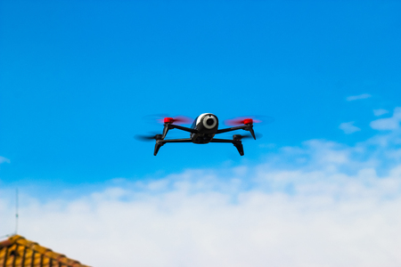 Photo for Drone flying overhead in cloudy blue sky over the roof of the house - Royalty Free Image