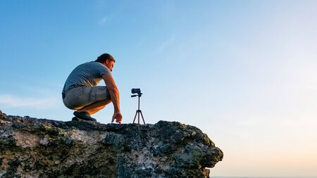 Photo for Travel photographer man sitting on the rock and taking nature video of beautiful sunset on the beach. Hiker tourist professional videographer on adventure vacation shooting by video camera on tripod. - Royalty Free Image