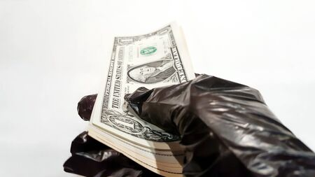Woman holds out her hand in a black protective glove with a bundle of money - dollars bank notes. Isolated on a white background. The collapse of the economy due to the coronavirus.