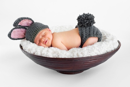Photo for Eight day old smiling newborn baby boy wearing bunny ears and a bunny tail diaper cover  He is sleeping on his stomach in a basket  Shot in the studio on an isolated white background   - Royalty Free Image
