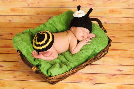 7ba94a9b697 Three 3 week old newborn baby girl wearing a crocheted black and yellow  bumblebee costume The. A sleeping newborn baby girl in chocetted cocoon  wearing hat ...