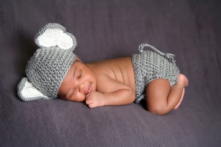 Photo pour Thirteen day old smiling newborn baby boy wearing a gray crocheted elephant hat and diaper cover  He is sleeping on his stomach on gray fleece fabric   - image libre de droit