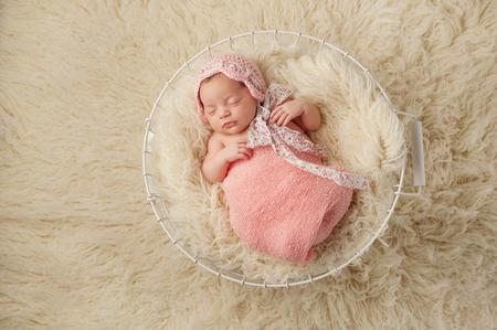01bb1d3b69d A portrait of a five week old newborn baby girl wearing a pink bonnet and  sleeping